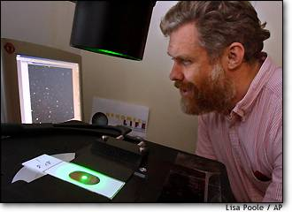 George Church, a professor of genetics at Harvard Medical School, looks at amplified single molecules of DNA with fluorescent computer imaging.
